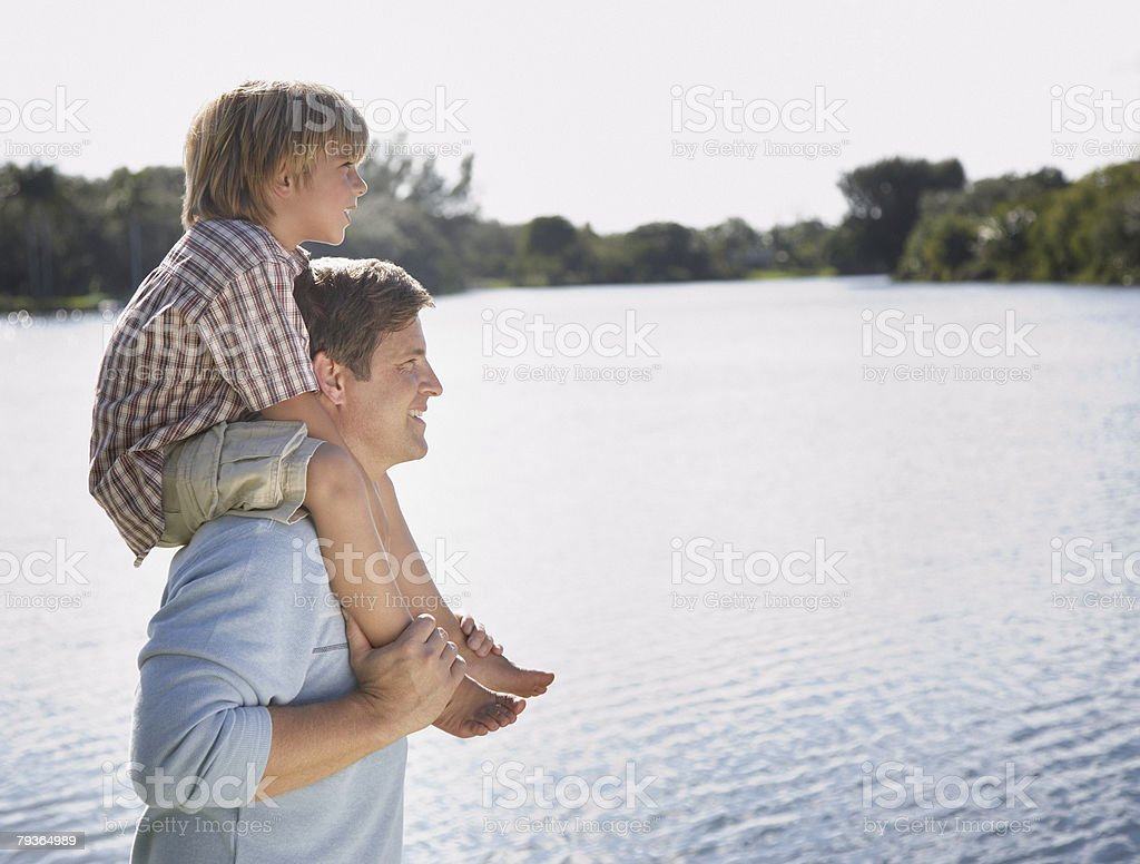 Man giving young boy shoulder ride outdoors at park by a lake royalty-free stock photo