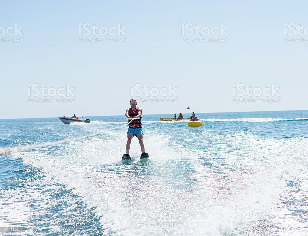 man glides on water skiing on the waves on the sea stock photo