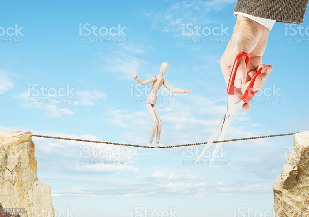 Man goes along rope but another cuts it with scissors stock photo