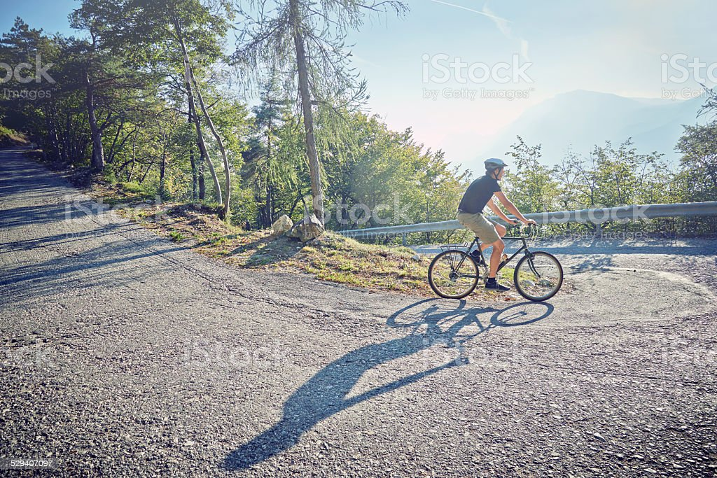 Man going down a switchback taking the curve inside stock photo