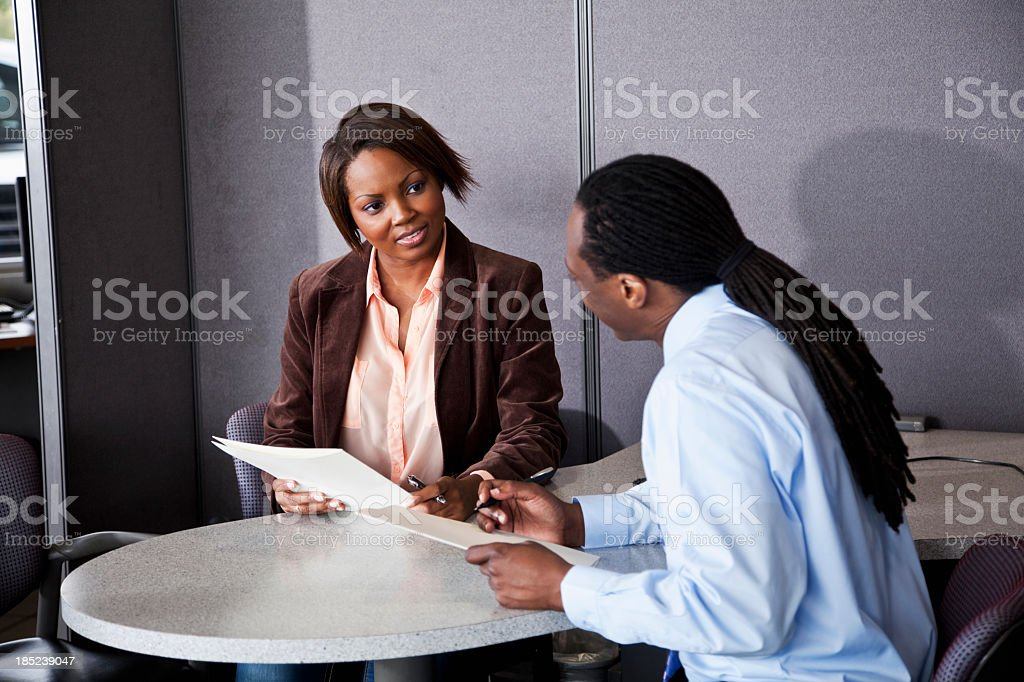 Man going over paperwork with customer royalty-free stock photo