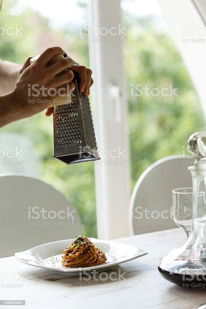 Man grating cheese over spaghetti stock photo