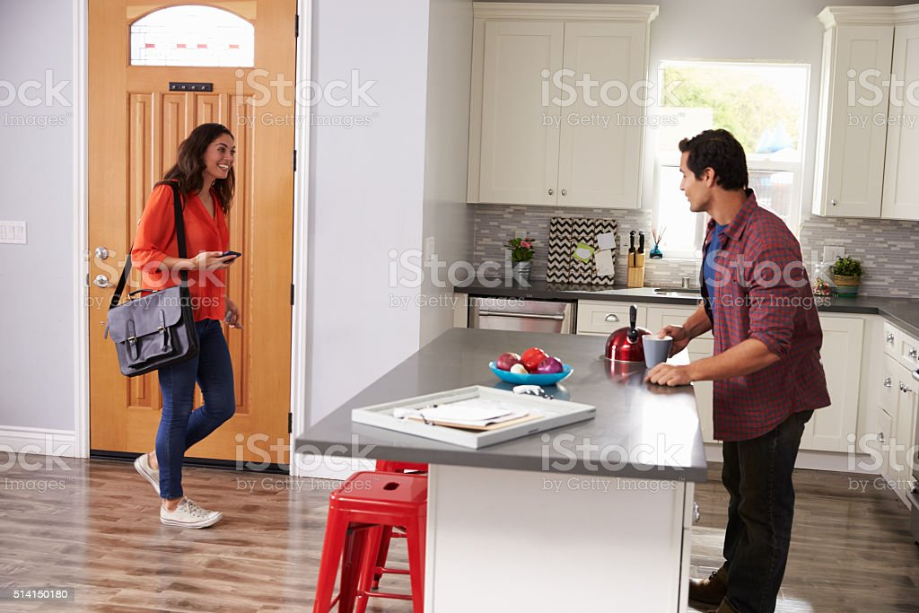 Man Greeting Woman Returning Home From Work stock photo