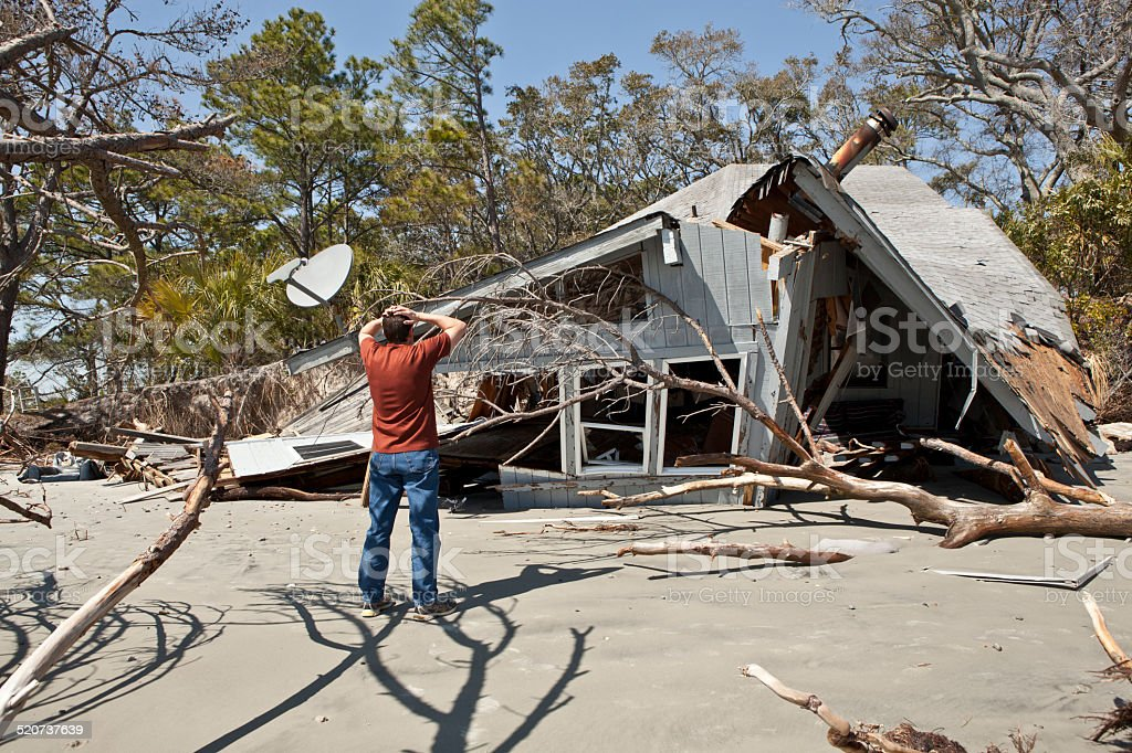 man grieving over destroyed house stock photo