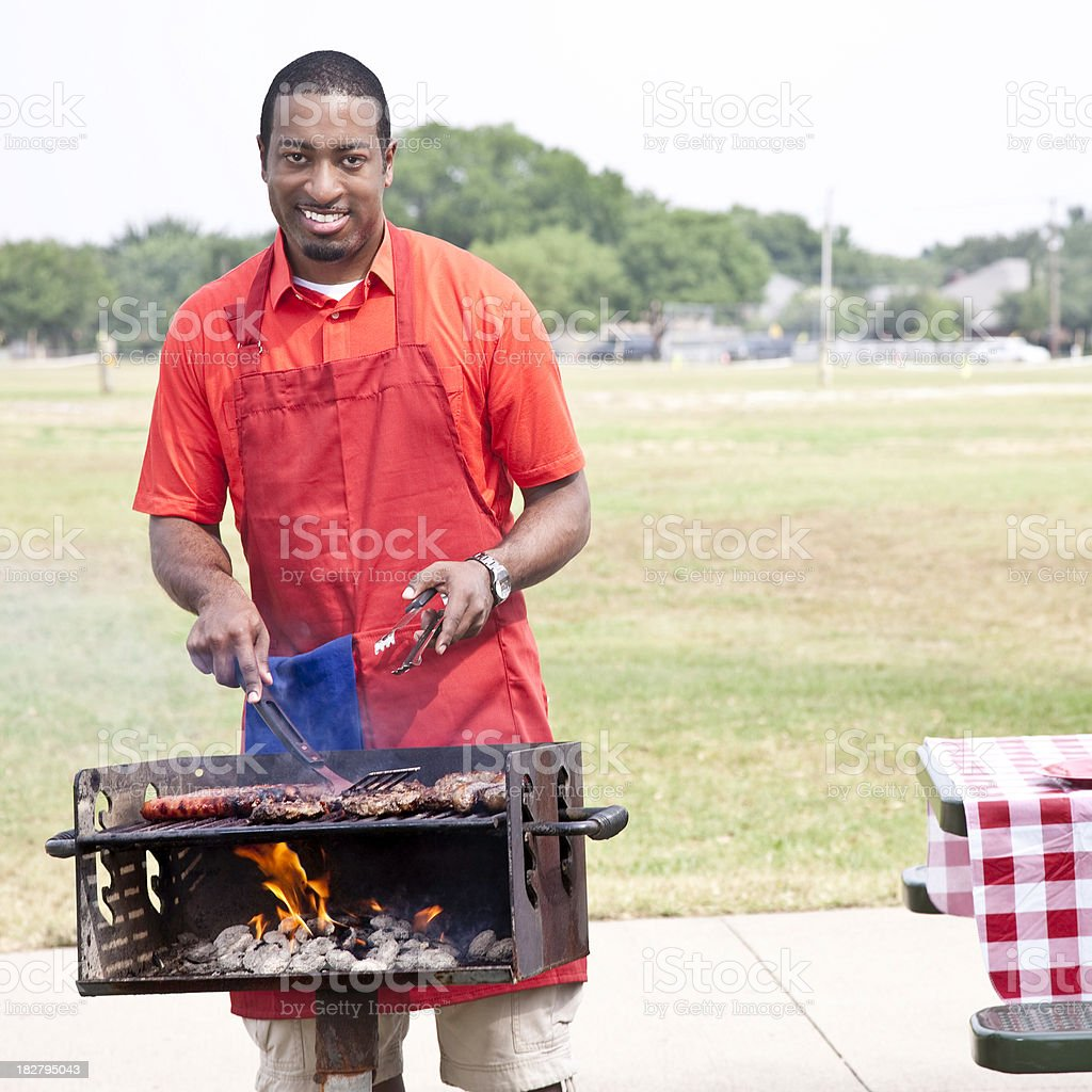 Man Grilling Burgers and Hot Dogs for Picnic at Park royalty-free stock photo