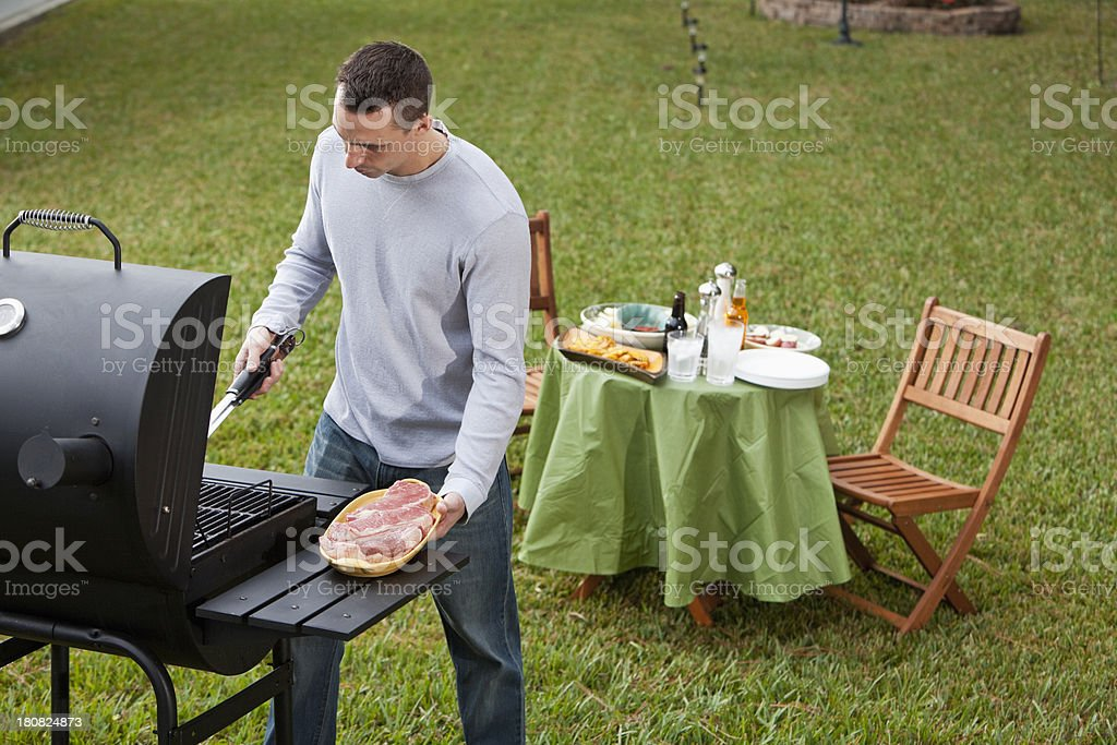 Man grilling steaks stock photo