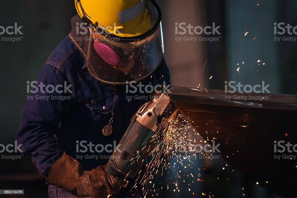 Man Grinding in workshop wearing hardhat and gloves. stock photo