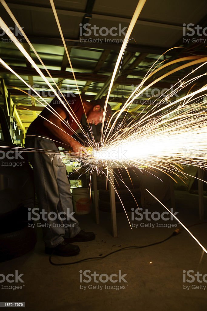 Man Grinding Metal in Shop stock photo