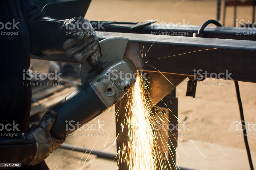 Man grinding metal with angle grinder stock photo