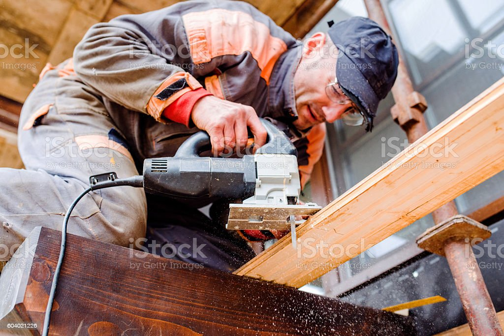 Man grinding planks of wood for home construction. stock photo