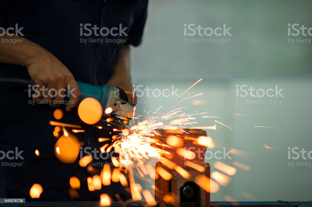 Man grinding steel with grinder. stock photo