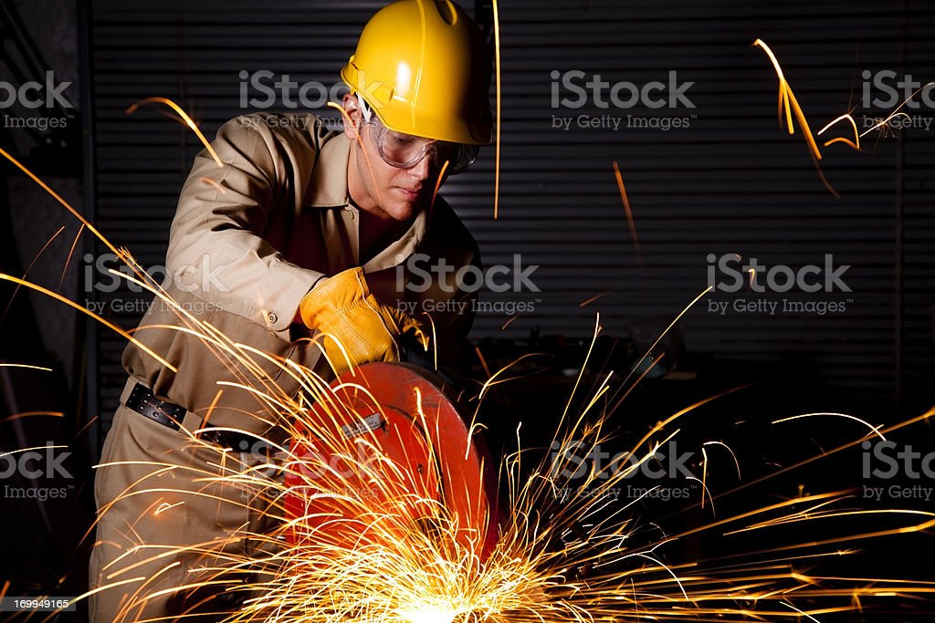 Man Grinding workshop wearing hardhat, safety goggles and gloves.  Sparks royalty-free stock photo