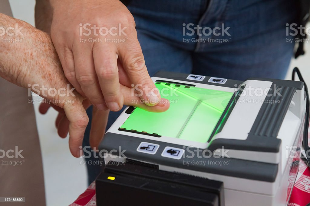Man guiding another in using a fingerprint scanner stock photo