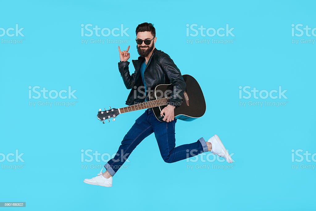 Man guitar player jumps while showing rock gesture stock photo