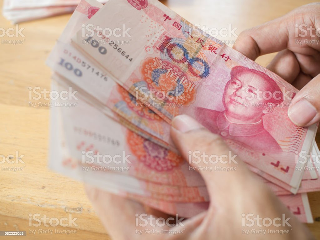 Man hand counting Chinese Yuan bank notes currency stock photo