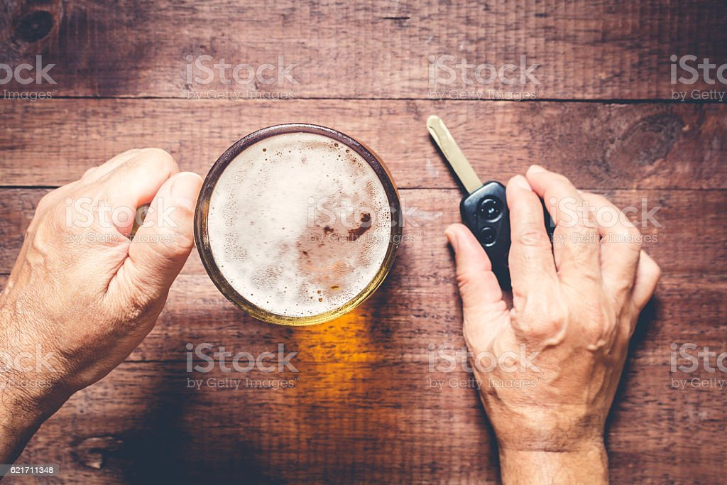 Man hand drinking beer and holding car keys stock photo