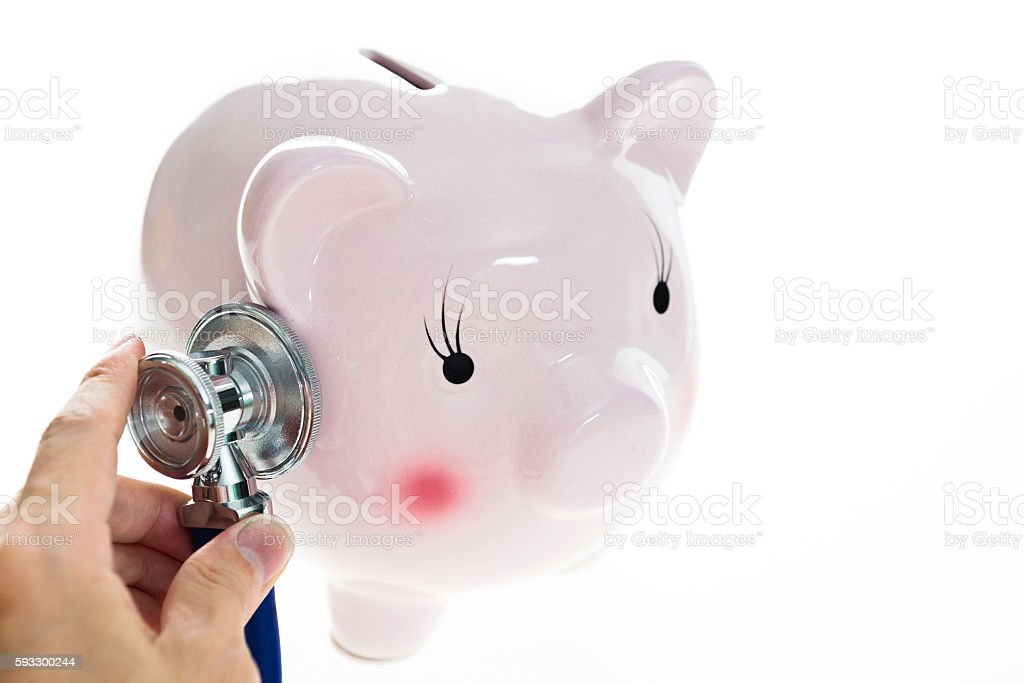 Man hand examining piggy bank with stethoscope stock photo