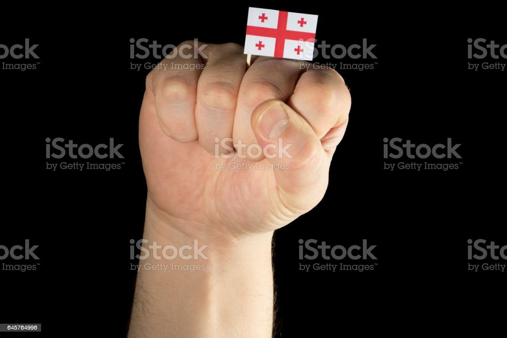 Man hand fist with Georgian flag isolated on black background stock photo