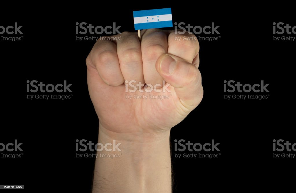 Man hand fist with Honduran flag isolated on black background stock photo