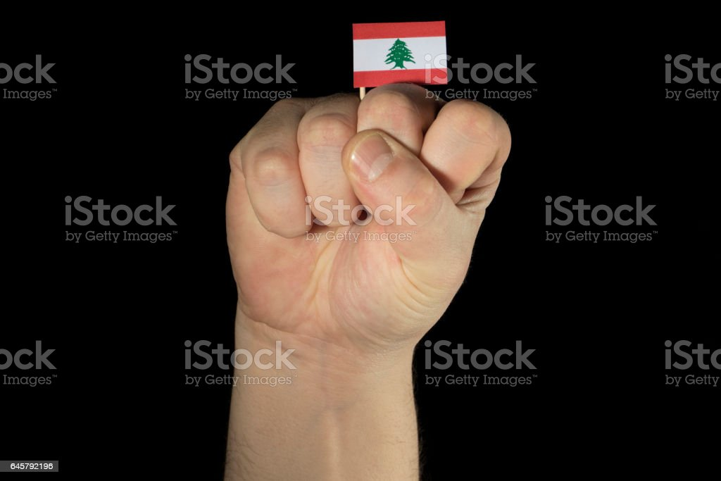 Man hand fist with Lebanese flag isolated on black background stock photo