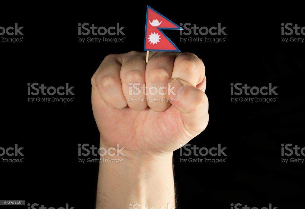 Man hand fist with Nepalese flag isolated on black background stock photo