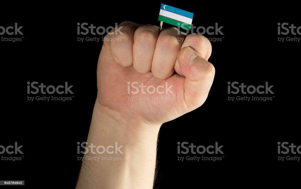 Man hand fist with Uzbekistan flag isolated on black background stock photo