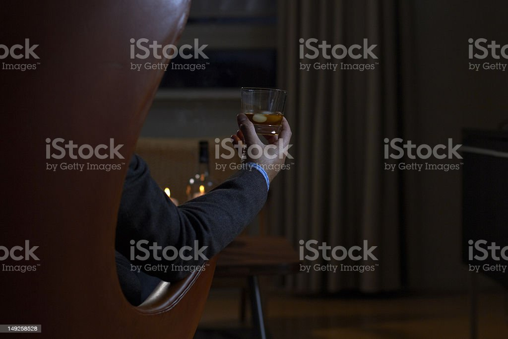 Man hand holding a glass of whisky in a fancy room stock photo