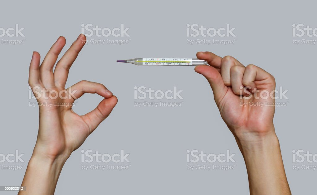 Man hand holding a mercury thermometer and shows sign OK stock photo