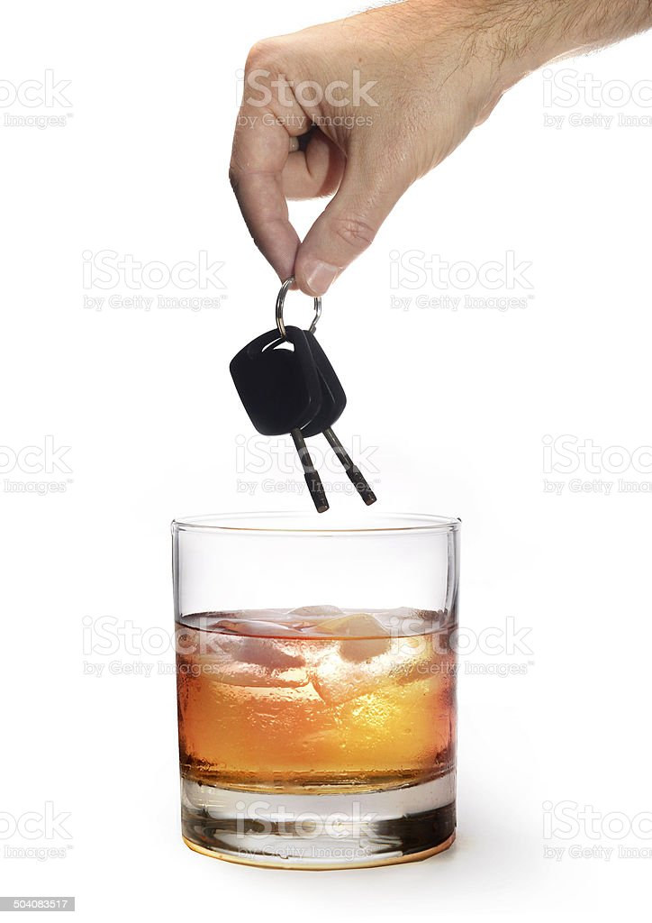 man hand holding car keys over glass of whiskey stock photo