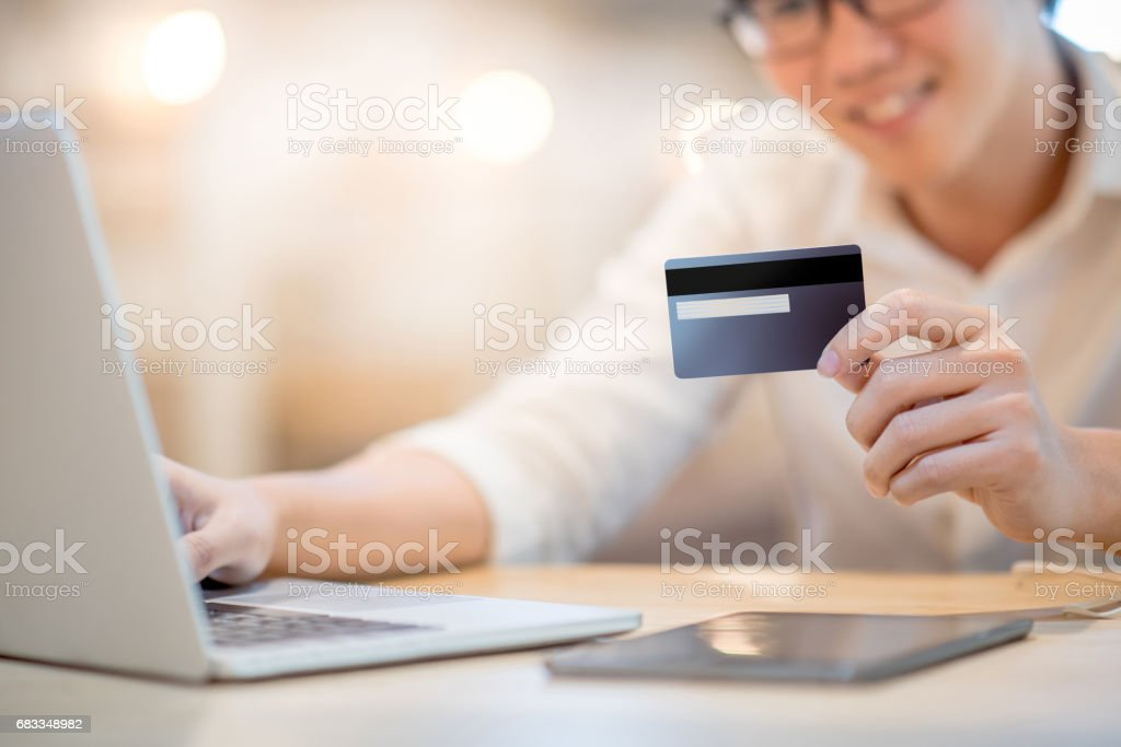 Man hand holding credit card and using laptop computer for online shopping stock photo