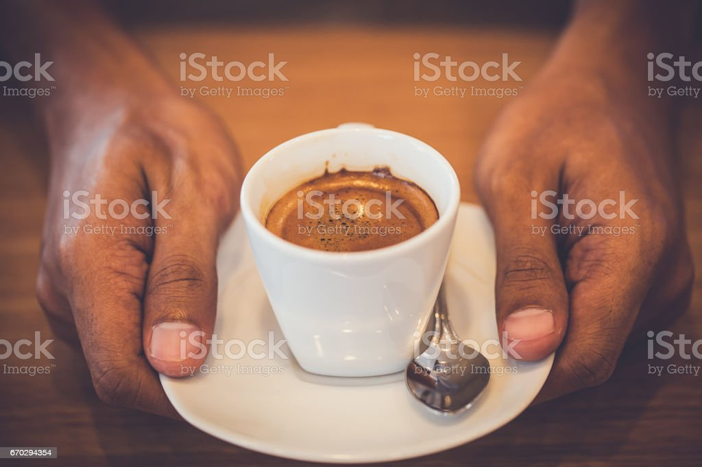 Man hand holding cup of coffee on wooden table stock photo