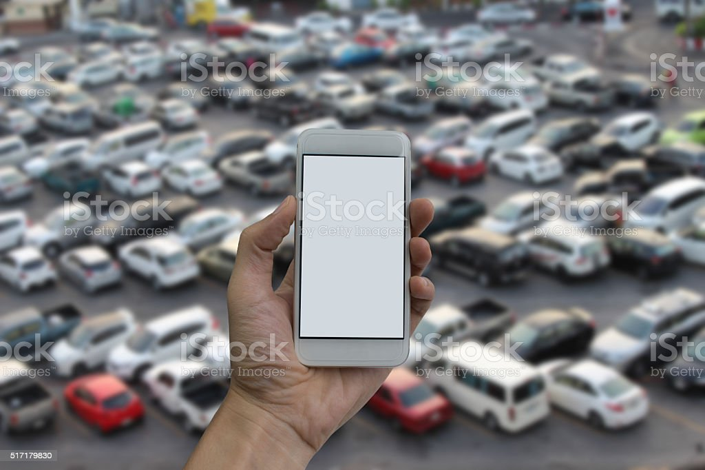 man hand holding empty screen of smart phone and parking stock photo