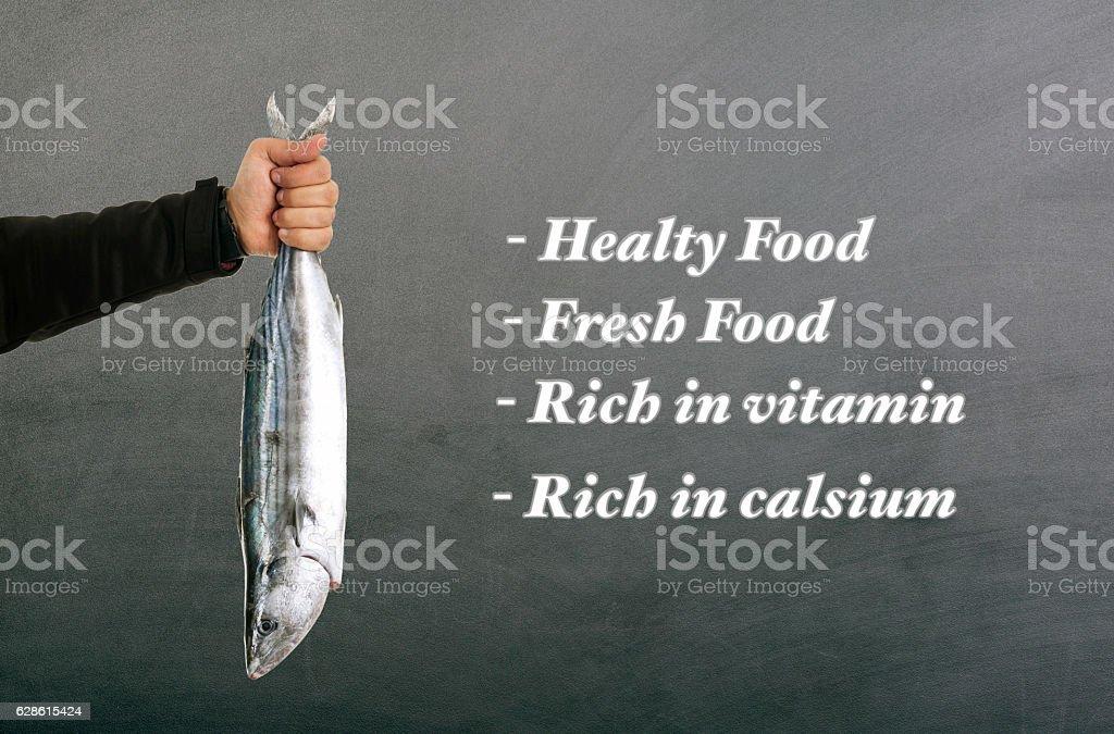 Man hand holding fresh fish on blackbaord stock photo
