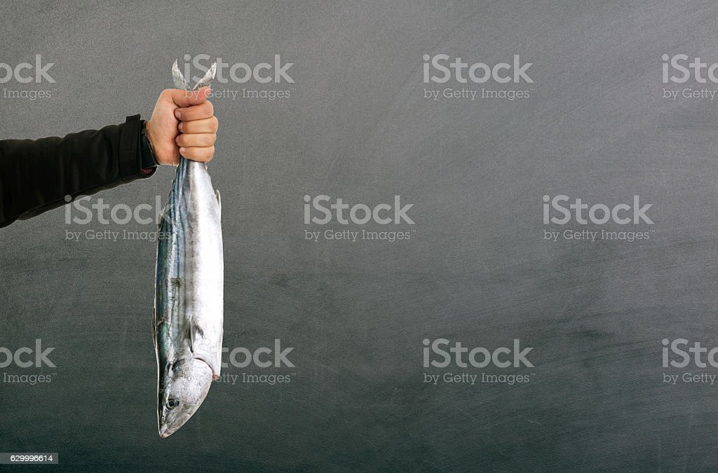 Man hand holding fresh fish on blackbaord stock photo