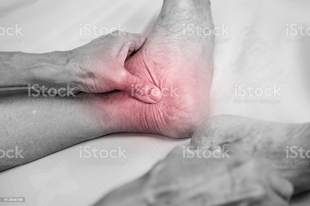 man hand holding he healthy foot and massaging ankle stock photo