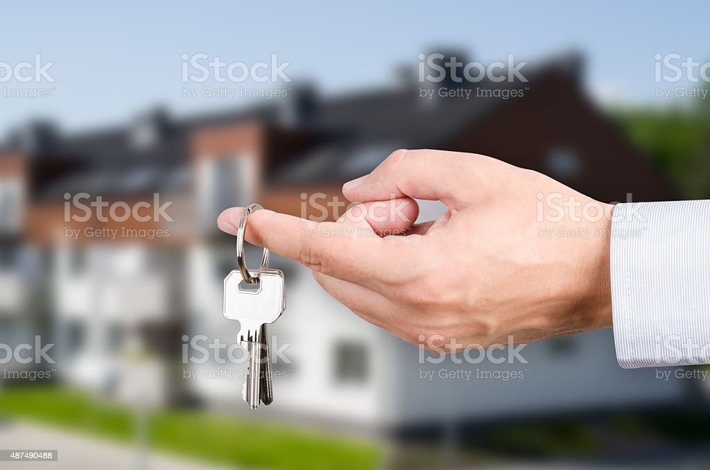 Man hand holding keys with to new house stock photo
