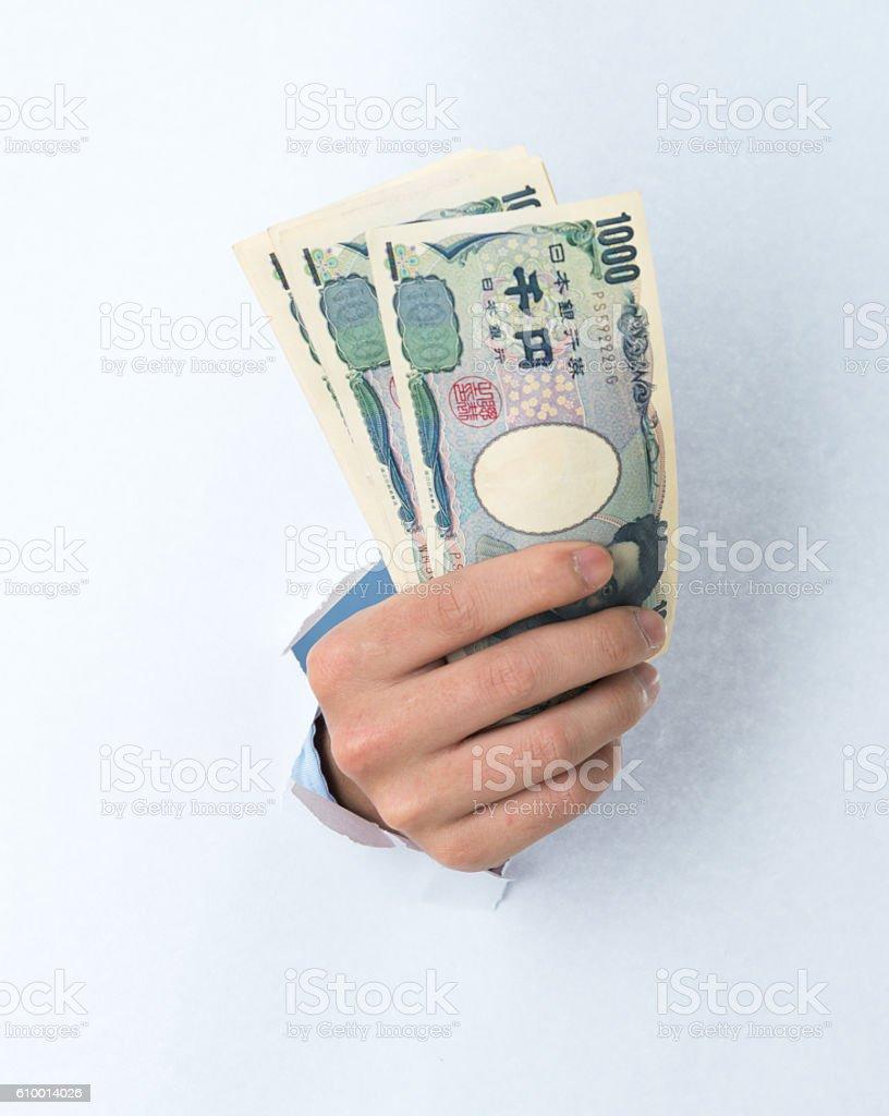 Man hand holding money through a hole stock photo