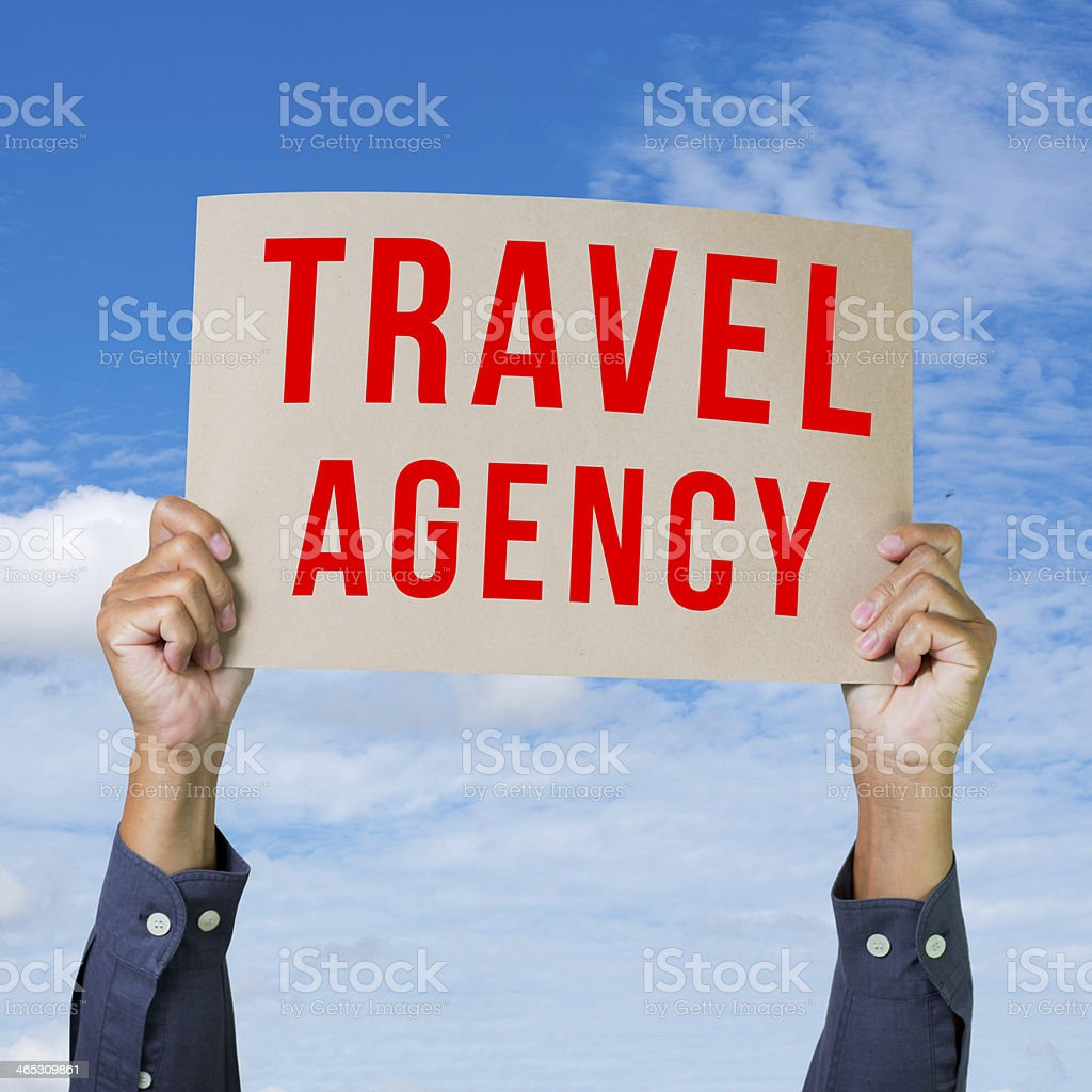 Man hand holding paper with travel agency word stock photo
