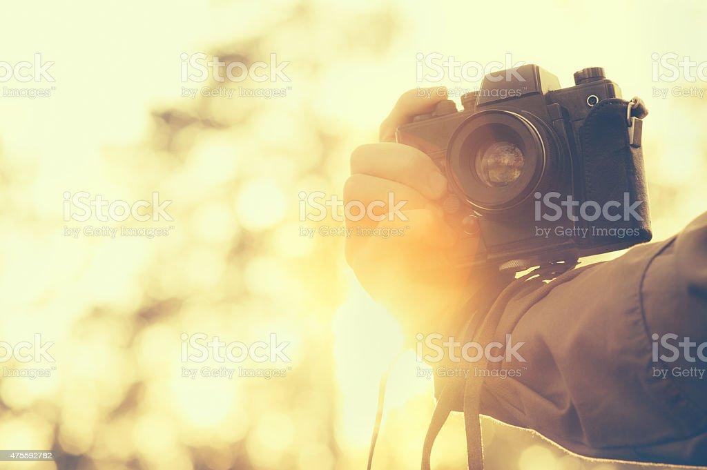 Man hand holding retro photo camera outdoor stock photo