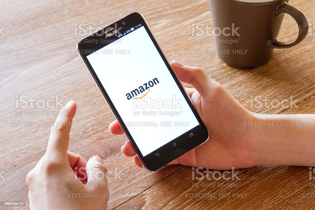 man hand holding screen shot of Amazon application stock photo