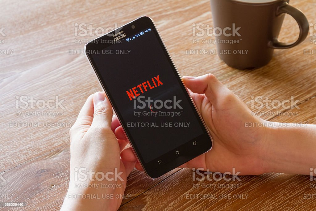 man hand holding screen shot of Netflix application stock photo