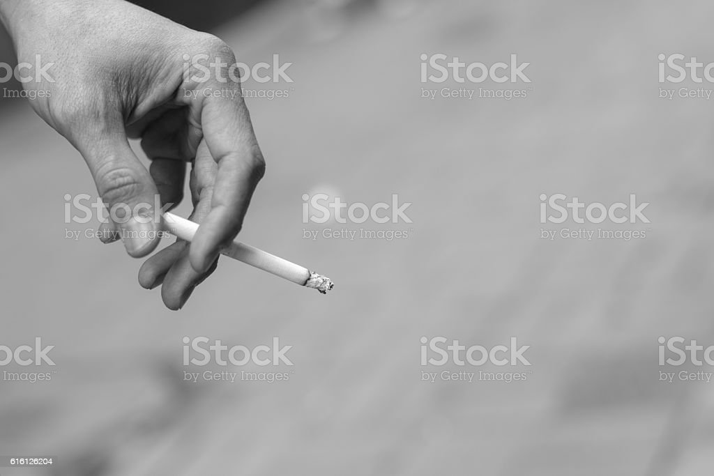 man hand holding smoking a cigarette stock photo