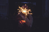 Man hand holding sparkler in the night.