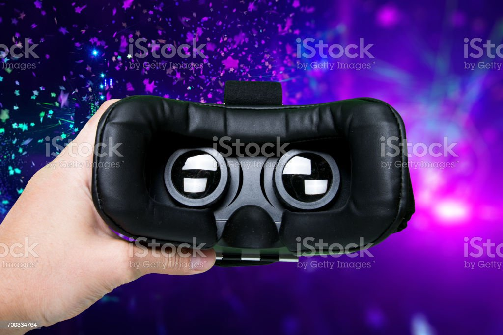 Man hand holding VR glasses on colorful background.Top view/Hands of man holding virtual reality goggles stock photo