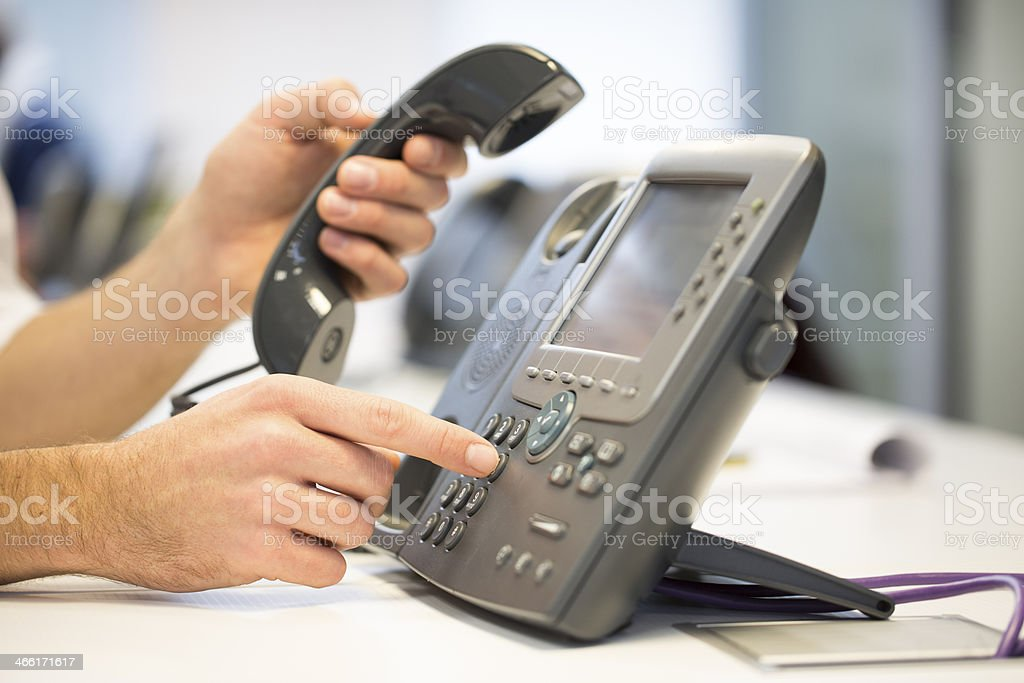Man hand is dialing a phone number, office Background stock photo