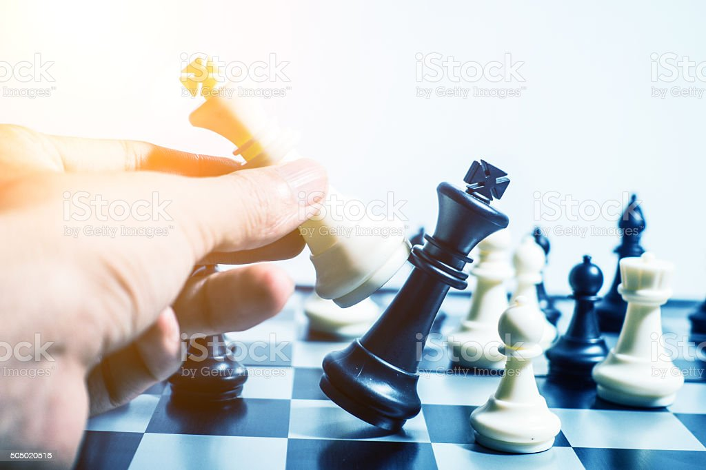 Man hand moving the king in a chess game stock photo