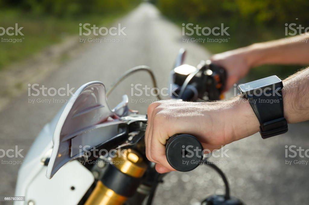 man hand on motorbike gas stock photo