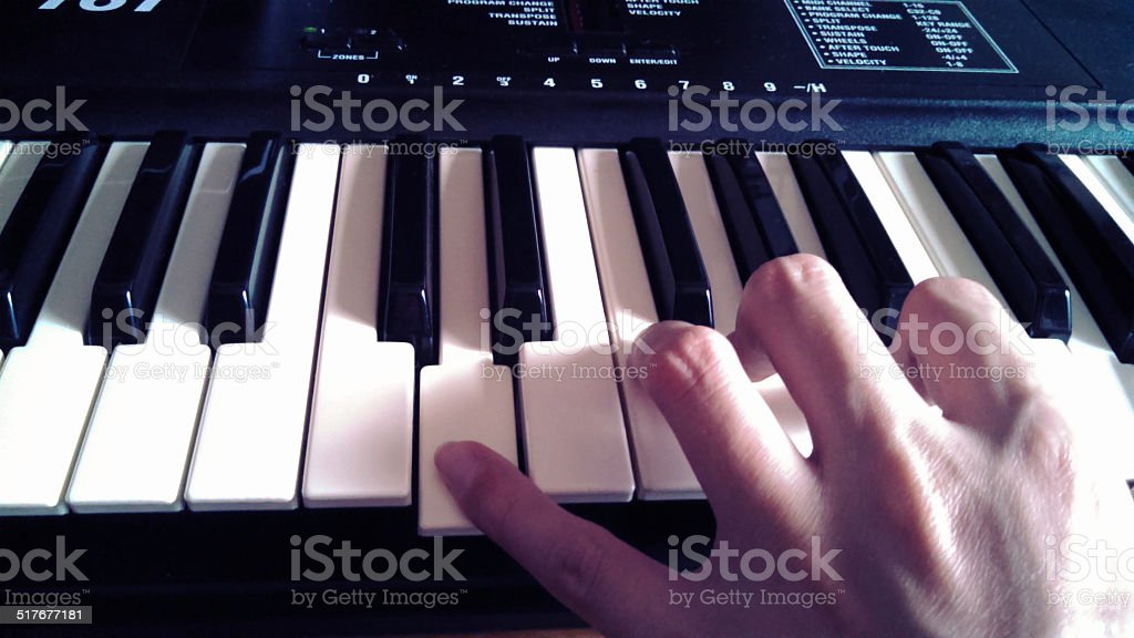 Man hand on the piano keys stock photo