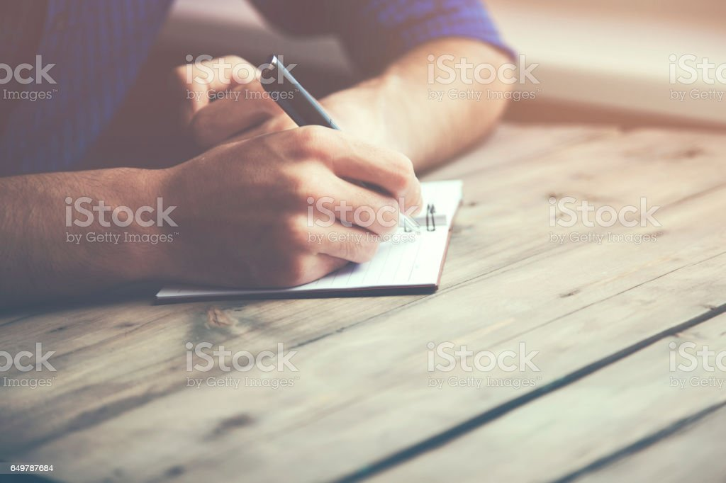 man hand pen and notebook on wooden table stock photo