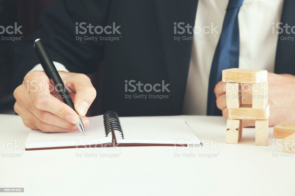 man hand pen and wooden blocks on table stock photo